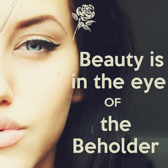 women half face with a small rose by the eye and the saying beauty is in the eye of the beholder