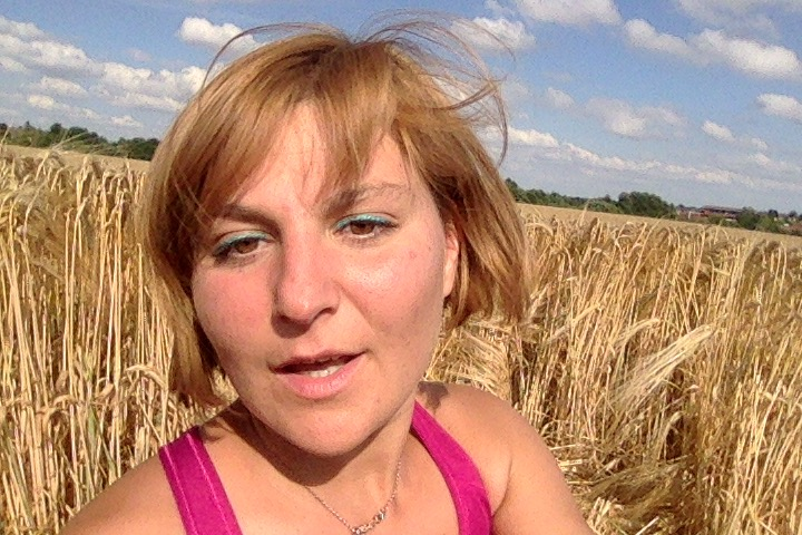 Delina in a corn field with gold hair colour and the wind at play