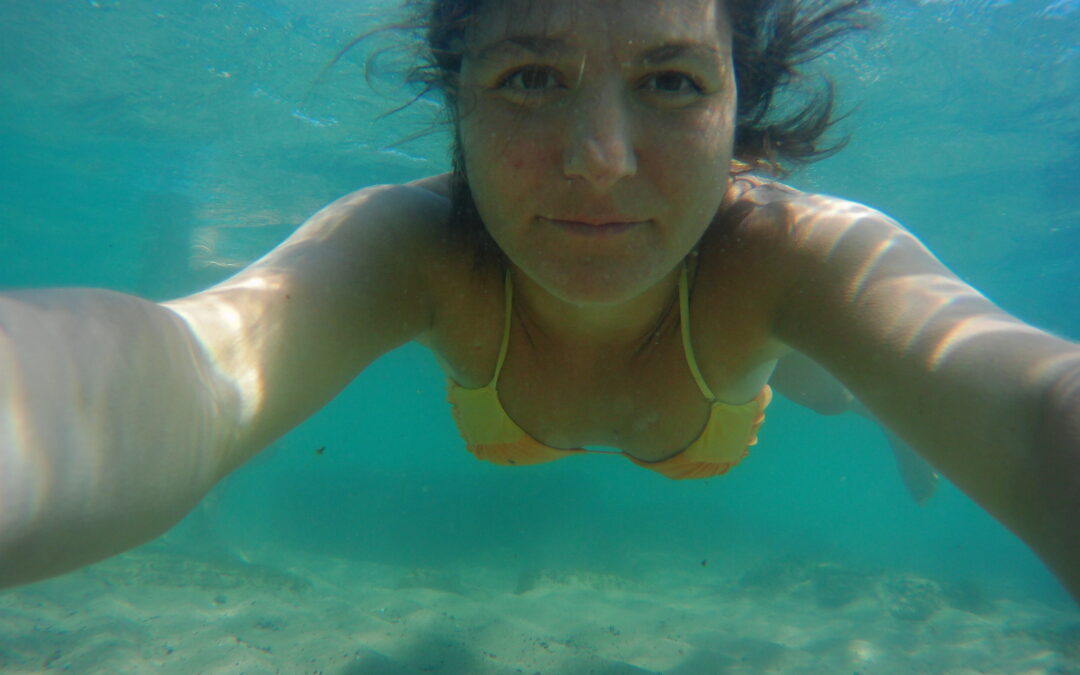 delina underwater looking at the camera as it's the mission of her life.