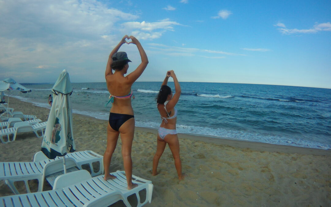 two girls at the beach making a heart shape with their fingers.